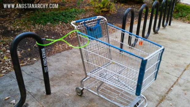 A shopping cart locked to a bike rack